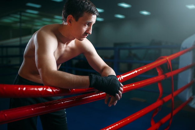 Boxer musculoso com bandagens pretas posa nas cordas do ringue