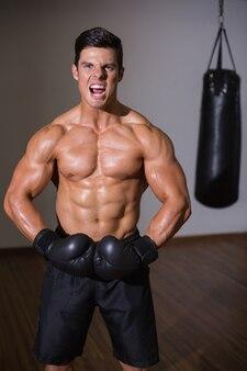 Boxer musculoso sem camisa gritando no health club