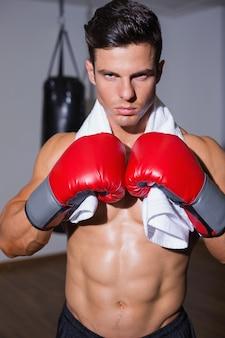 Boxer musculoso sem camisa na posição defensiva