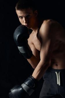 Boxer se inclinou para frente em um fundo preto com luvas