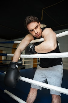 Boxer treinando em um ringue de boxe. olhando de lado.