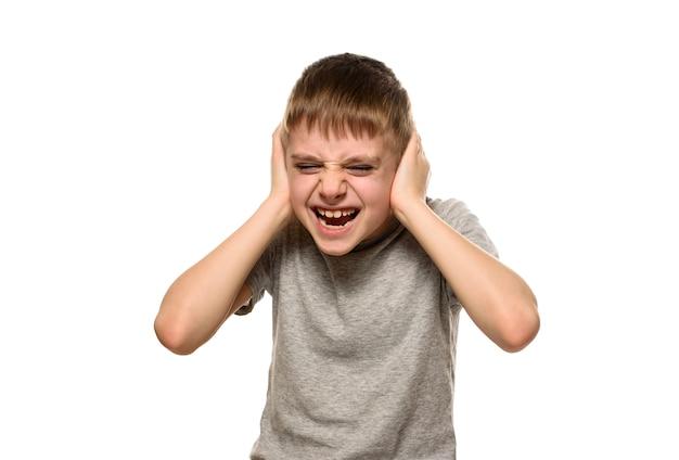 Boy fechou os ouvidos com as mãos e gritou furiosamente. estudante impertinente. isolar
