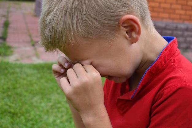 Boy ficou ofendido. menino chora de perto.
