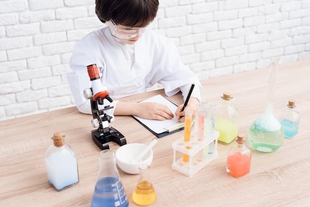 Boy registra os resultados do experimento em um caderno.
