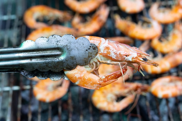 Braçadeira segurar camarão grelhado com outro no fundo de churrasco