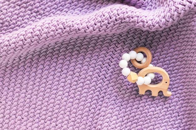 Bracelete de manta tricotada à mão e mordedor de bebê em madeira, elefante com contas de borracha. cobertor macio. parto. conceito de recém-nascido. camada plana, vista superior com espaço de cópia.