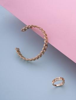 Bracelete e anel em forma de corrente com fundo azul e rosa em tons pastel