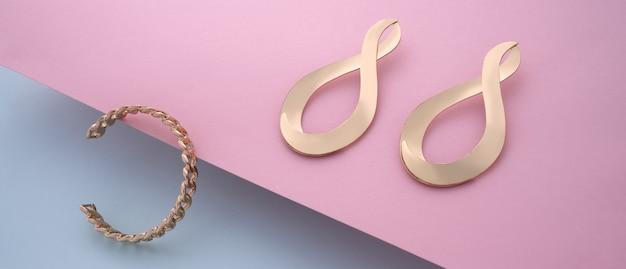 Bracelete em forma de corrente dourada e um par de brincos modernos em rosa e azul