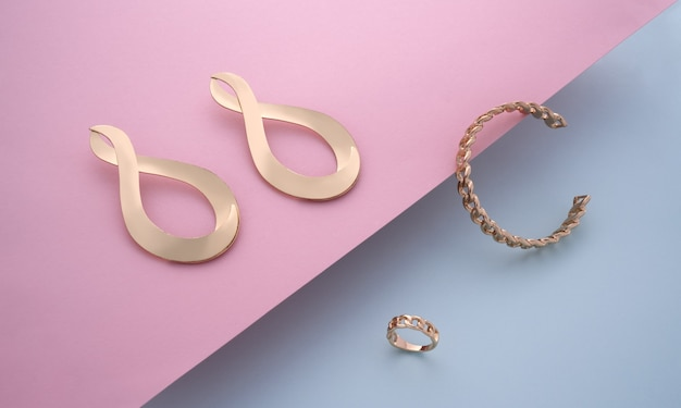 Bracelete em forma de corrente e anel com par de brincos modernos dourados em fundo rosa e azul