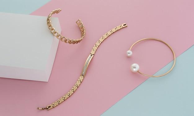 Braceletes dourados modernos em tons pastel rosa azul e fundo de papel branco