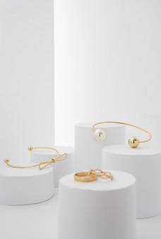 Braceletes modernos dourados em plataformas de papel branco