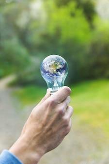 Braço adulto mantendo a lâmpada com o planeta