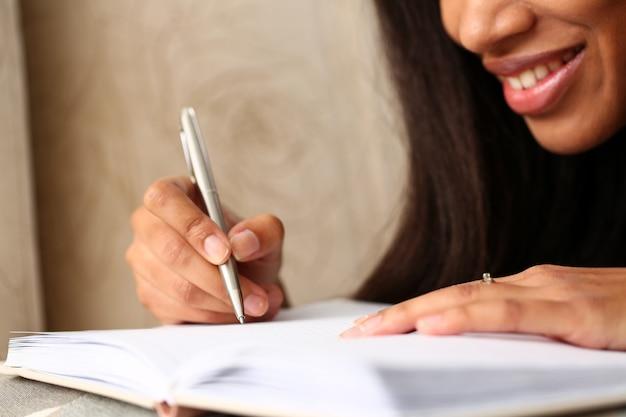 Braço da mulher negra escrever história no caderno