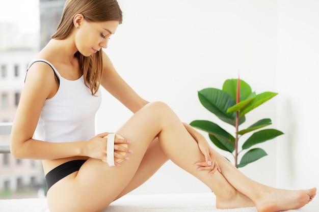 Braço da mulher segurando o pincel seco no topo da perna, tratamento para celulite e escovação a seco.