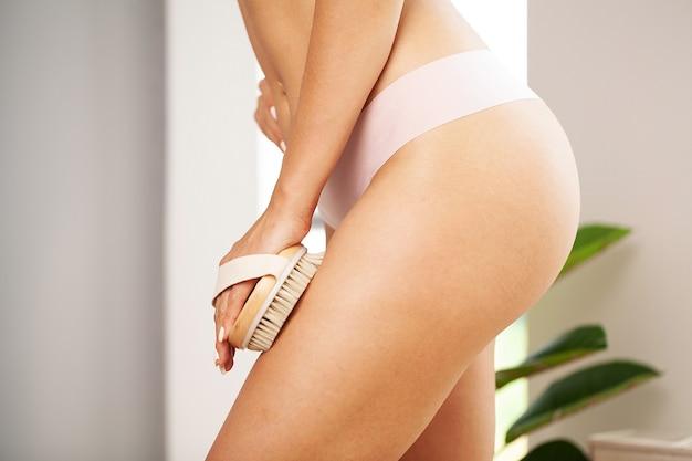 Braço da mulher segurando o pincel seco no topo da perna, tratamento para celulite e escovação seca.
