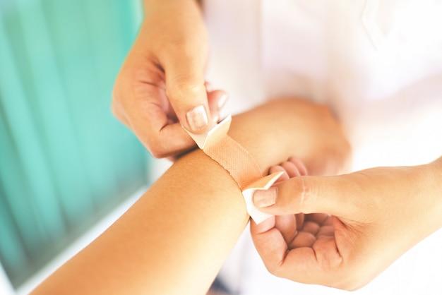 Braço de bandagem de ferida de cotovelo pela enfermeira - cuidados de saúde de lesão de pulso de primeiros socorros e conceito de medicina