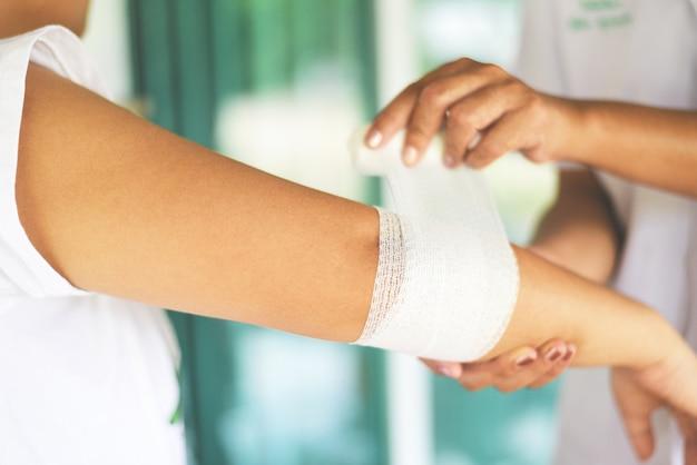 Braço de bandagem de ferida de cotovelo por enfermeira