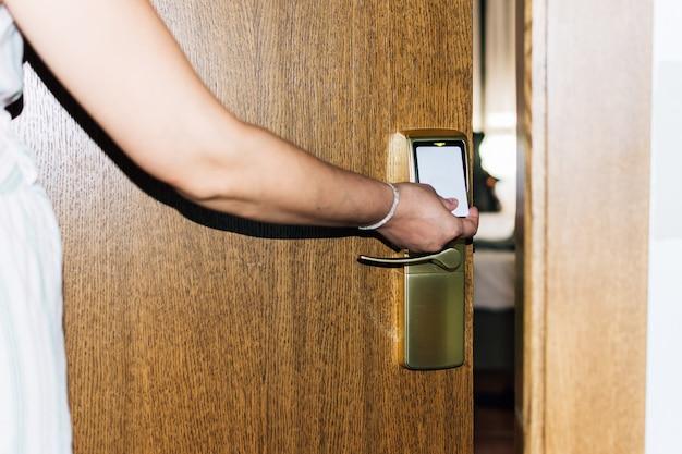 Braço de mulher abrindo a porta do quarto de hotel com um cartão
