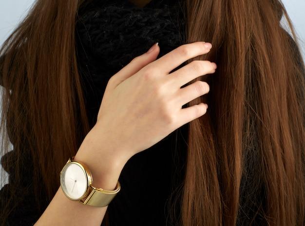 Braço de mulher com relógio de ouro