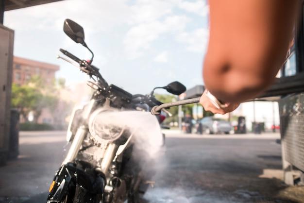 Braço de mulher segurando a motocicleta de lavagem de pistola de pressão com água e sabão de pressão em um posto de gasolina.