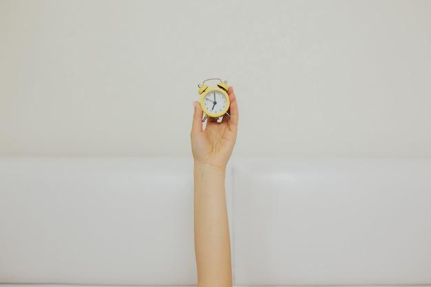 Braço de mulher segurando o pequeno relógio amarelo enquanto estava deitado na cama.