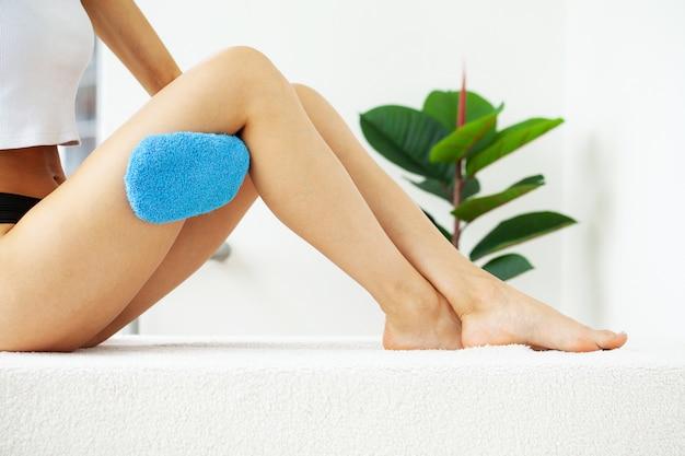 Braço de mulher segurando o pincel seco azul no topo da perna, tratamento de celulite e escovação a seco.