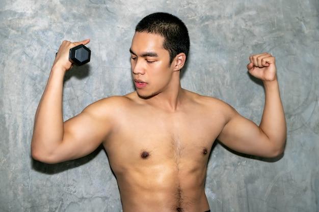 Braço de treino perfeito homem asiático atlético fisiculturista forte com halteres em fundo.