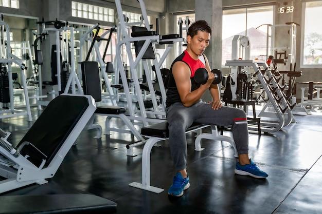 Braço de treino perfeito homem asiático atlético fisiculturista forte com halteres no ginásio.