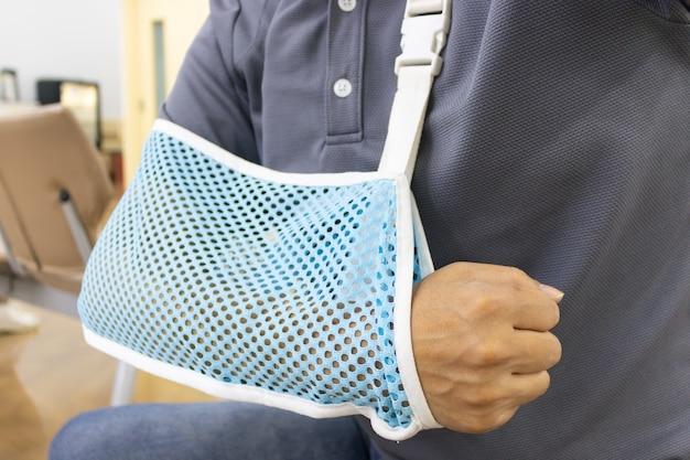 Braço do homem ferido que está usando uma malha de suspensão