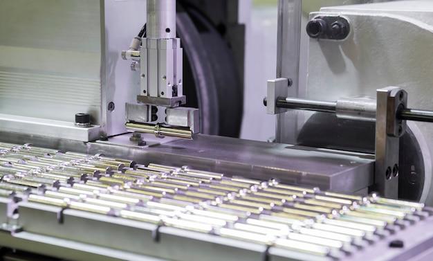 Braço do robô escolhe pequenas peças usinadas para o próximo processo de fabricação