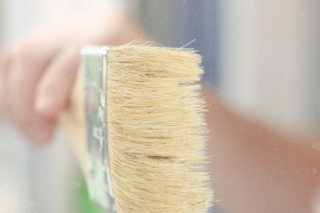 Braço do trabalhador sorridente segurar escova closeup