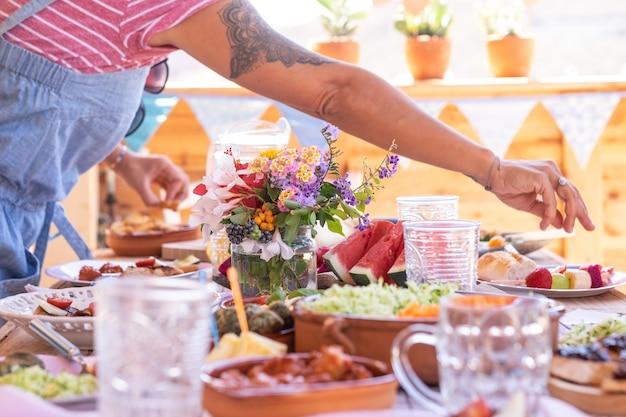 Braço feminino com tatuagem preta tirando algumas frutas da mesa. povos caucasianos, desfrutando de um brunch ou refeição juntos. frutas e vegetais na mesa de madeira. luz do sol ao ar livre no terraço