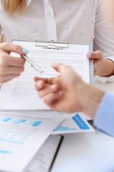 Braço feminino no formulário de contrato de oferta de terno na área de transferência