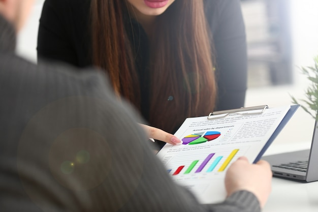 Braço feminino segurando o ponto de caneta prata no gráfico financeiro