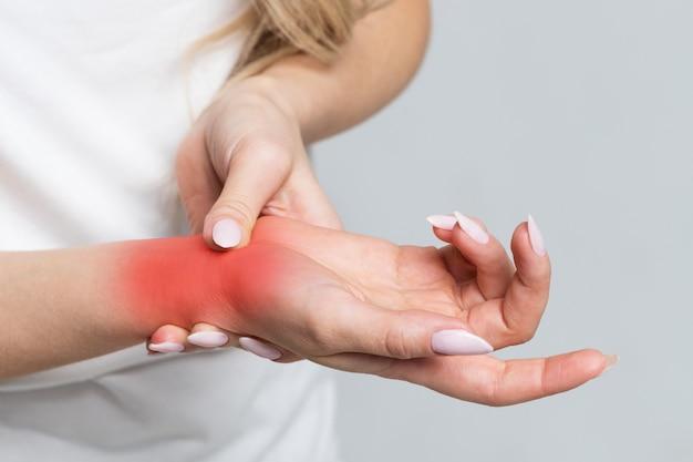 Braço feminino segurando o pulso dolorido causado por trabalho prolongado no computador