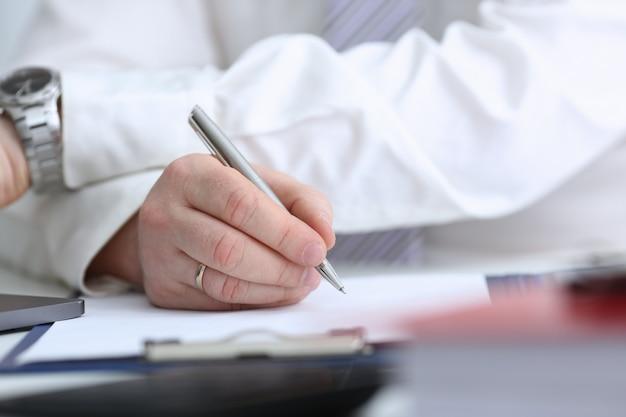 Braço masculino de terno e gravata com caneta prata