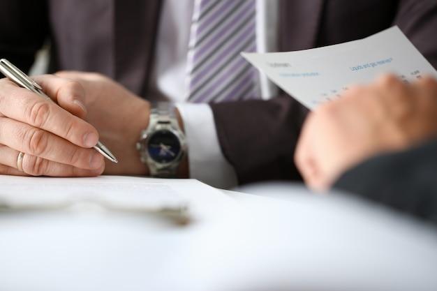 Braço masculino de terno e gravata preenchido formulário cortado