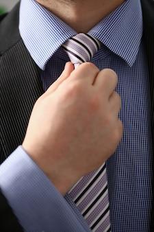 Braço masculino em terno marrom conjunto gravata closeup