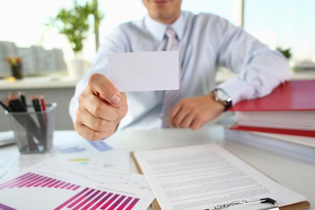 Braço masculino no terno dá cartão de visita em branco