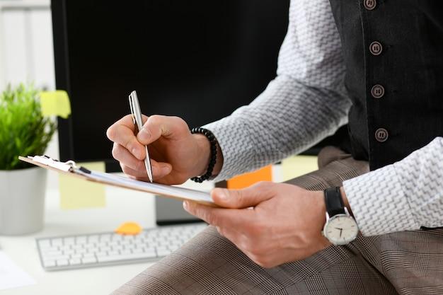 Braço masculino no terno segura caneta e bloco de prata