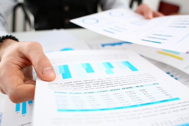 Braço masculino segurando papéis com estatísticas de negócios