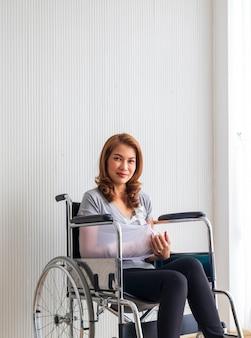 Braço quebrado mulher asiática com tipoia de braço patrocinado nas mãos, sentado em uma cadeira de rodas idéias para acidentes lesões e cuidados de saúde studio filmado em branco