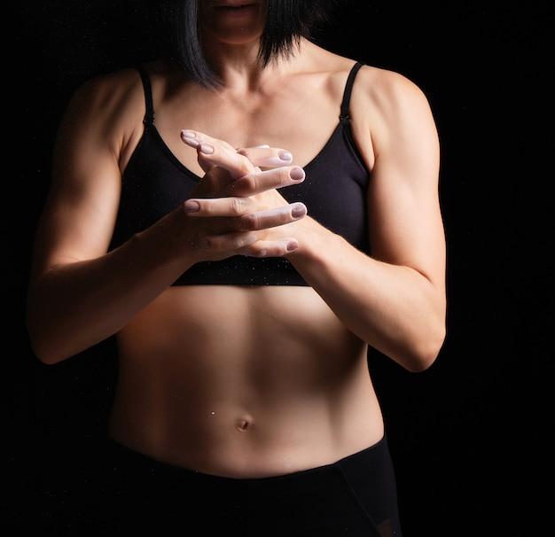 Braços atléticos com veias e o torso muscular de uma jovem garota com cabelos pretos