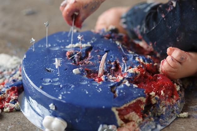Braços de bebê caucasiano aniversário enquanto destruindo e esmaga o bolo de esmalte azul