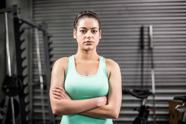 Braços de cruzamento de mulher atlética infeliz no ginásio