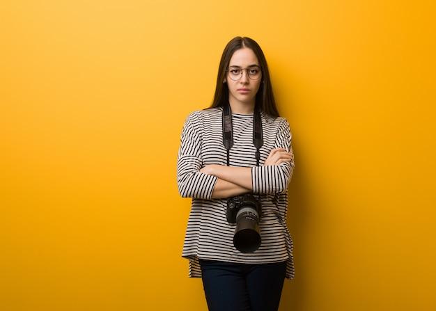 Braços de cruzamento de mulher jovem fotógrafo relaxado