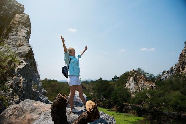 Braços de mulher estendidos em uma rocha de montanha