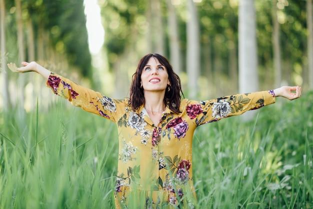 Braços de mulher levantados, apreciando o ar fresco na floresta verde