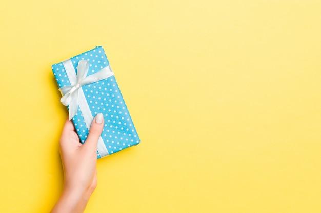 Braços de mulher segurando a caixa de presente com fita colorida no fundo da mesa amarela, vista superior e copie o espaço para você projetar