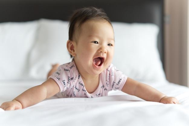 Braços de rastejamento e de espalhamento do bebê asiático bonito novo na cama no quarto.